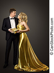 Couple Give Present Gift Box, Fashion Man and Woman Beauty Portrait, Well Dressed in Black Suit and Gold Dress