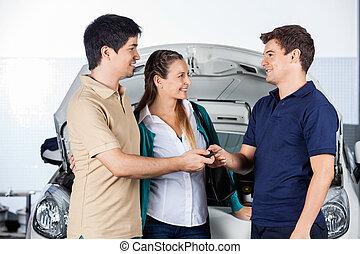 Couple Giving Car Keys To Mechanic