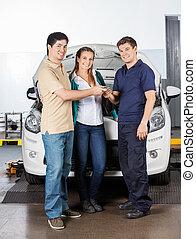 Couple Giving Car Keys To Technician