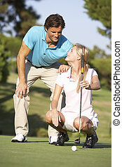 Couple Golfing On Golf Course Lining Up Putt On Green