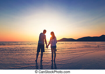 couple hand hold on the beach between sunset.