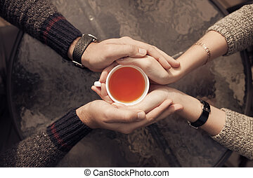 Couple hands holding cup of tea. Top view.