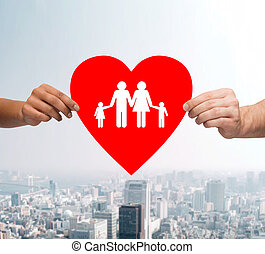 couple hands holding red heart with family