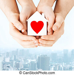 couple hands holding white paper house