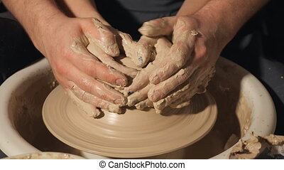 couple hands making clay jug on potter's wheel, close up