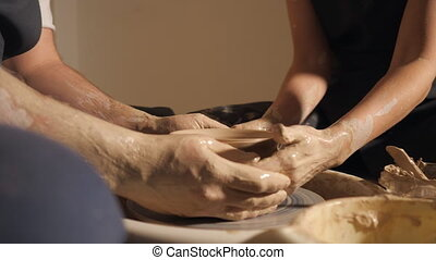 couple hands making clay jug, slow motion