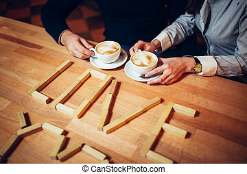 couple hands of coffee on a wooden table