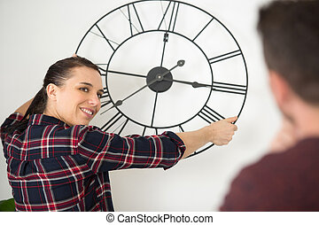 couple hanging a clock on the wall