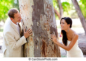 Couple happy in love playing in a tree trunk outdoor park