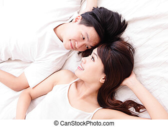 couple happy smile looking to each other in bed