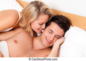 Couple has fun in bed. Laughter, joy and eroticism in the...