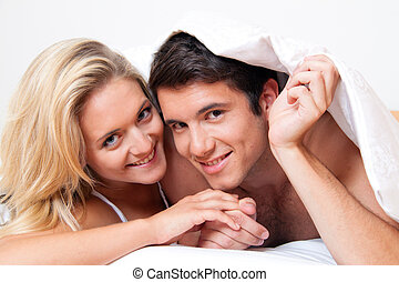 Couple has fun in bed. Laughter, joy and eroticism