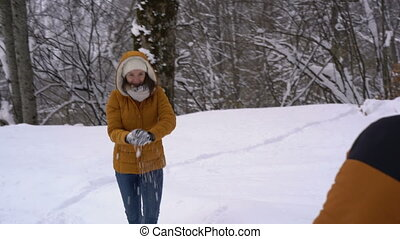 Couple has snowball fight in winter forest