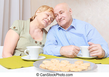 Couple has tea with biscuits