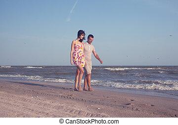Couple have a walk along the shore of sea or ocean
