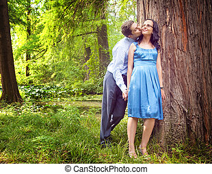 Couple having a candid romantic kiss outdoors