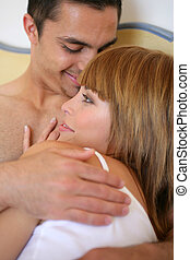 Couple having a cuddle in bed