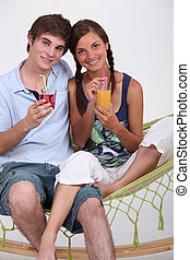 Couple having a drink in a hammock.