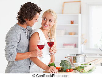 Couple having a glass of red wine while looking at each...