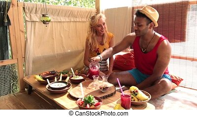Couple having a lunch on tree house at the beach