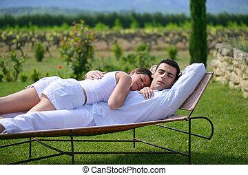 Couple having a nap on sun lounger