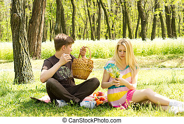 Couple having a picnic date, sitting on the grass