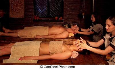 Couple having Ayurvedic spa treatment. Two masseuses start to massage face.