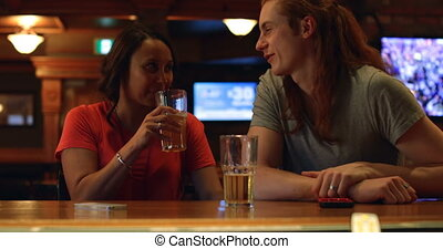 Couple having beer at bar counter 4k - Couple having beer at...