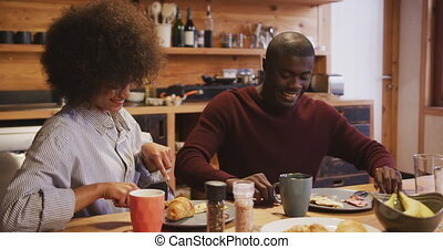 Couple having breakfast at home - Front view of a smiling ...