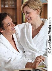 Couple having breakfast dressed in bathrobe