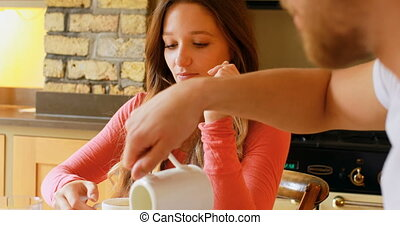Couple having coffee on dining table in kitchen 4k - Couple ...