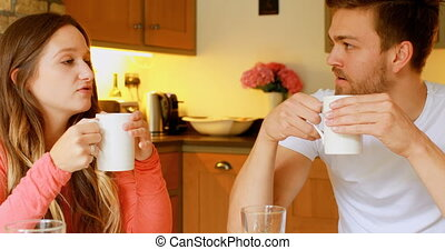 Couple having coffee on dining table in kitchen 4k