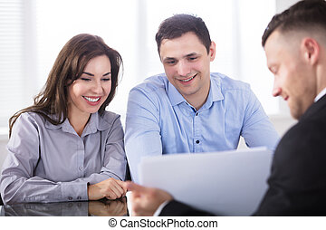 Couple Having Discussion With Advisor In Office