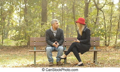 adult couple having an argument, they are sitting on a bench outdoor in a park, they are fighting then she goes away throwing the engagement ring to him breaking the relashionship