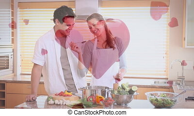 Couple having fun and cooking at home with digital hearts