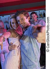 Couple Having Fun In Busy Bar