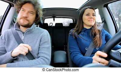 Couple having fun in car dancing - Woman driving car dancing...