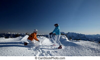 couple having fun in snow - couple in skiing clothes having...
