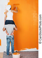 Couple having fun painting a wall - Young couple is having...