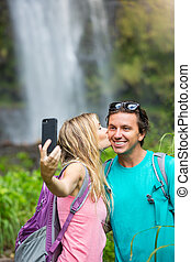 Couple having fun taking pictures together outdoors on hike...