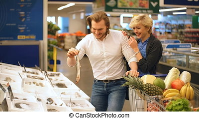 Couple having fun while choosing fish in the supermarket.