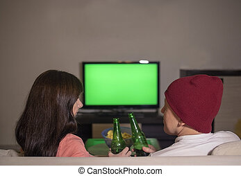 Couple having fun with a bottle watching TV sitting on the couch in the room, blurred background, green screen