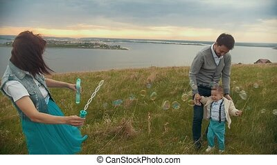 Couple having fun with baby on the field, baby laughing soap bubbles