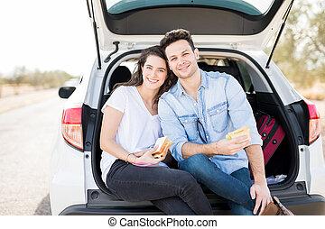 Couple having lunch break during road trip