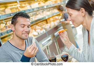 Couple having meal, looking at the cheese they are eating