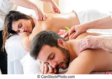 Couple having relaxing body massage in spa.Two therapists...
