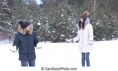 Couple having snowball fight in snow in winter forest.