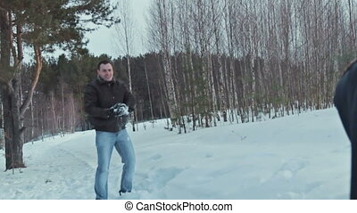 Couple having snowball fight in snow in winter forest,...