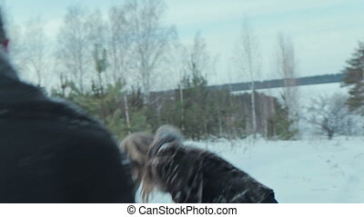 Couple having snowball fight in snow in winter forest