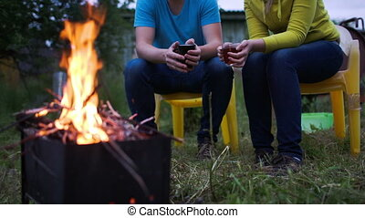 Couple having tea by the fire in the evening